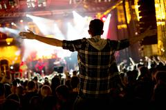 Crowd of people at concert in front of the stage - stock photo