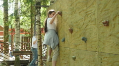 Girl climbing on a pendant wall in the adventure park & falls down, Full HD shot Stock Footage