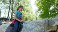 A girl riding in a saddle on horseback in the adventure park, Full HD shot - stock footage