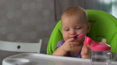 The child sits and plays with the spoon - stock footage