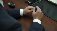A man sits in the conference room, nervous, twirling a pen in hand Stock Footage