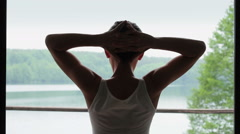 Woman looking out big bright window with arms outstretched HD - stock footage