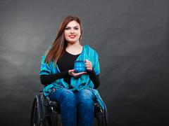 Woman invalid girl on wheelchair holds tea mug - stock photo