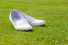 particular of white wedding shoes on grass - stock photo