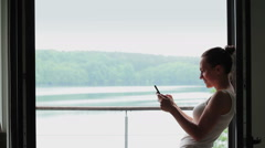 Woman using mobile smart phone in front of the big window HD Stock Footage