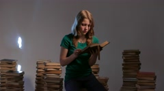 Teen girl is surrounded by books and reading. 4K UHD Stock Footage