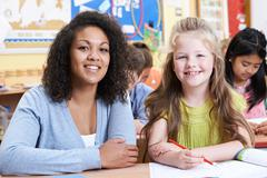 Portrait Of Teacher With Female Elementary School Pupil In Class - stock photo