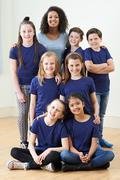 Group Of Children With Teacher Enjoying Drama Workshop Together Stock Photos
