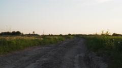Walking backwards between rural field on dirt road Stock Footage