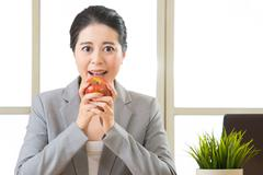 Young asian businesswoman eating healthy snack, apple - stock photo