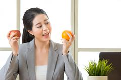 Young asian businesswoman eating healthy snack Stock Photos