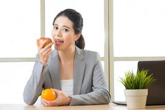 Young asian businesswoman eating healthy snack - stock photo