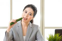 Young asian businesswoman eating healthy snack, cucumber - stock photo