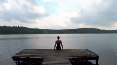 Young woman with arms outstretched sitting by the lake, rear view HD - stock footage