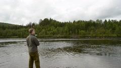 salmon fisherman reeling in the fishing line - stock footage