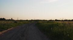 Walking forward between rural field on dirt road Stock Footage