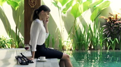 businesswoman cellphone drink edge pool villa outdoor K HD - stock footage