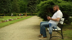 Angry man talking in the cell phone, sitting on a bench at the park Stock Footage