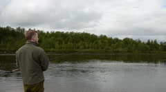 Fisherman reeling in the long fishing line from the river stream Stock Footage