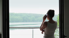 Silhouette of woman on the phone in front of the big window HD Stock Footage