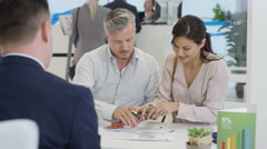 4K Modern city bank, couple talking to adviser & signing document Stock Footage
