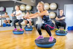 Focused group training squats on half ball at fitness gym Kuvituskuvat