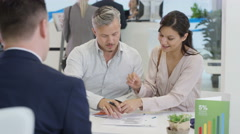 4K Modern city bank, couple talking to adviser & signing document - stock footage