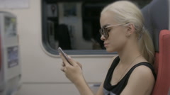 Young tired blonde woman using smartphone in subway train at metro - stock footage
