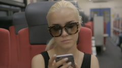 Young tired blonde woman using smartphone in subway train at metro Stock Footage