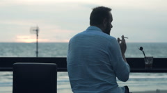 Young man smoking cigarette sitting on cafe on the beach Stock Footage