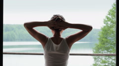 Woman looking out big bright window with arms outstretched HD Stock Footage