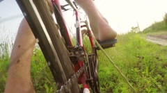 Slow motion cyclist man cyclist starts to go through the tall grass at sunset, l Stock Footage