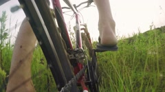 Slow motion cyclist man rides through the tall grass at sunset, low point shooti Stock Footage