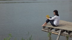 Woman sitting on the board table near water Stock Footage