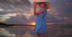 Black woman in sun dress dancing and smiling on Costa Rica beach at sunset Stock Footage
