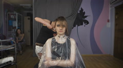 Beautiful girl in a beauty salon. Professional stylist makes to the woman a new Stock Footage
