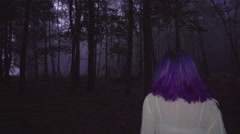 Back view of beautiful woman in shirt and purple hair walking in dark forest. - stock footage