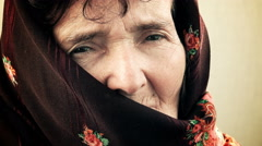 Sad and pensive old woman with a scarf on half of her face Stock Footage