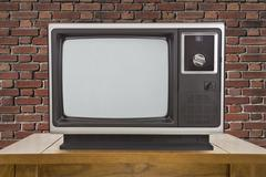 Old Television and Table with Brick Wall - stock photo