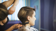 Beautiful girl in a beauty salon. Professional stylist makes to the woman a new - stock footage