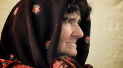 Pensive old woman with a shawl over her head turn and looks in camera Stock Footage