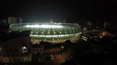 Amazing architecture of modern sports arena illuminated at night, aerial shot Arkistovideo