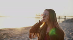 Young beautiful girl in sunglasses on sunset smiling on camera Stock Footage
