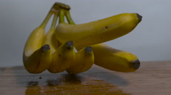 Fresh yellow bananas on stem bounce off of each other in slow motion - stock footage