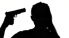 Girl taking a gun to her temple. Silhouette. White Stock Footage