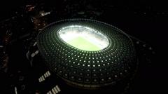 Illuminated football arena and urban lights, night time cityscape, big city - stock footage