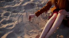 Beauty girl draws a heart on the sand on sunset beach Stock Footage