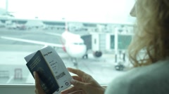 Woman Holding Passport and Boarding Pass at Airport Stock Footage