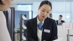 4K Modern city bank with friendly adviser talking to customer.  Stock Footage