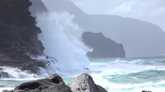 SLOW MOTION: Angry waves splashing into big ocean cliff rising out of the sea - stock footage